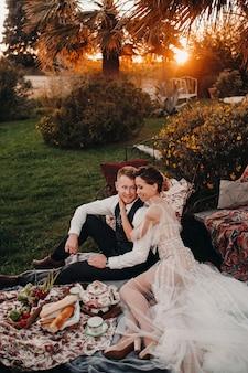 Diner het bruidspaar op de picknick. een koppel is aan het ontspannen bij zonsondergang in frankrijk. bruid en bruidegom op een picknick in de provence.