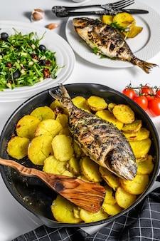 Diner met gegrilde zeebrasem vis, rucola salade met tomaten gebakken aardappelen