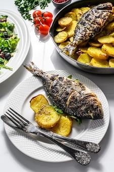 Diner met gegrilde zeebrasemvis, rucola-salade met tomaten, gebakken aardappelen