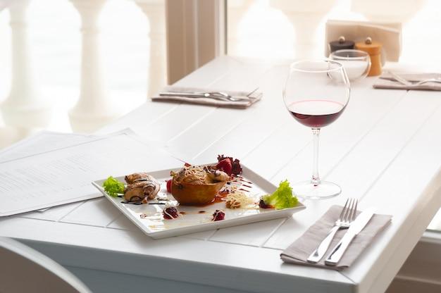 Diner of lunch met schotel per persoon. luxe witte interieur van restaurant. rode wijn en kip met peer