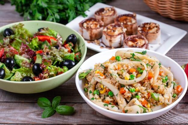 Diner: salade, gebakken inktvis met rijst en dessert op tafel