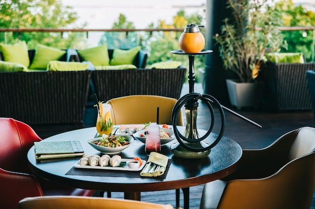 Diner set sushi rolt salades cocktails waterpijp zijaanzicht