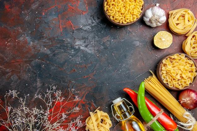 Diner voorbereiding met ongekookte pasta's cayennepeper in elkaar gebonden met touw olie fles citroen knoflook op gemengde kleur tabel footage