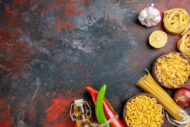 Diner voorbereiding met ongekookte pasta's cayennepeper in elkaar gebonden met touw olie fles citroen knoflook op gemengde kleurentafel
