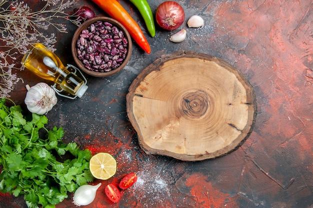 Diner voorbereiding met voedsel en bonen olie fles en een bos van groene citroentomaat en houten dienblad op gemengde kleurentafel