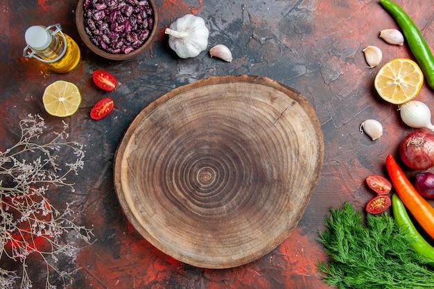 Diner voorbereiding olie fles bonen citroen en een bos van groen op gemengde kleurentafel