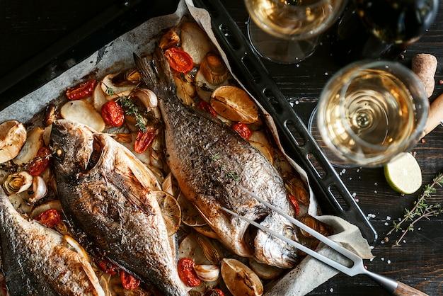 Dinerconcept met twee glazen witte wijn, gebakken vissen
