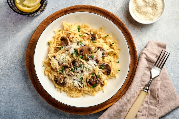 Dineren italiaanse pasta risoni, champignons, saus, parmezaan, tijm, knoflook, olijfolie, in wit bord