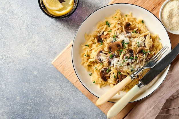 Dineren italiaanse pasta risoni, champignons, saus, parmezaanse kaas, tijm, knoflook, olijfolie, in wit bord white