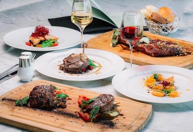 Dineropstelling met middelgrote en zeldzame steaks garnalen in saus gegrilde kippenpoot