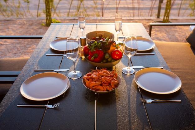 Dinerterras voor de familie wijn met miauw bij zonsondergang eten op het terras bij zonsondergang