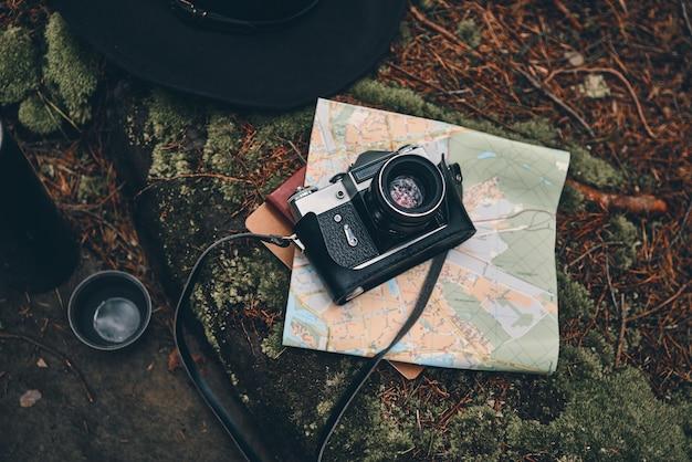 Dingen die je nodig hebt in het bos. close-up bovenaanzicht van digitale camera, kaart, hoed en geïsoleerde drankcontainer op de grond in het bos