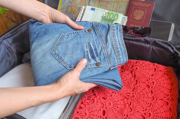 Dingen stapelen in een koffer voordat je op reis gaat. het concept van reizen. dingen in de koffer.