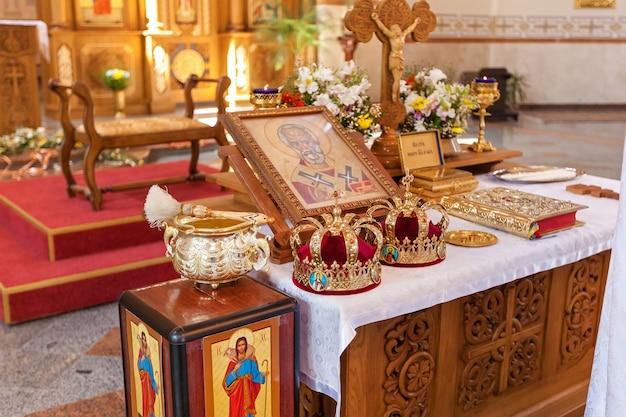 Dingen voor de bruiloft in de kerk. twee kronen, een icoon, wijwater. bruiloften in de kerk