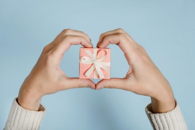 Dinsdag geven help donatie ondersteuning vrijwilligersconcept met vrouwelijke handen en roze geschenkdoos aan