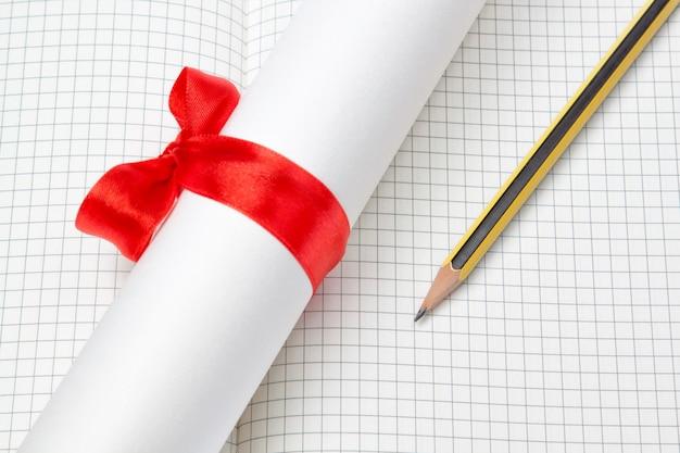 Diploma aan de notebook en potlood in een kooi.