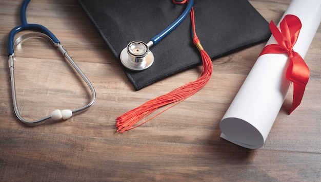 Diploma, afstuderen hoed en stethoscoop op de houten achtergrond.