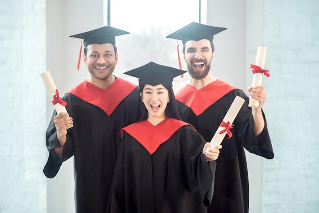 Diploma uitreiking. afgestudeerden in mortarboards zien er gelukkig en vreugdevol uit