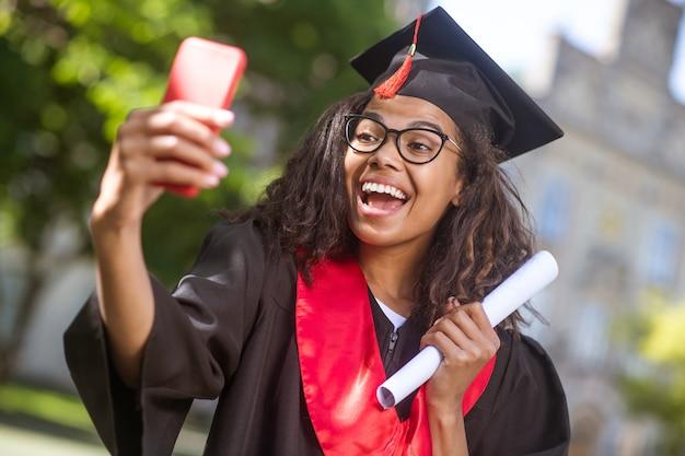 Diploma uitreiking. een meisje dat een videogesprek voert en goed nieuws deelt over afstuderen