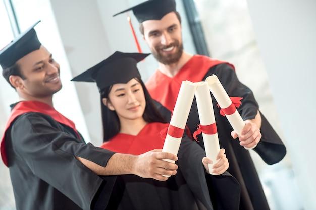 Diploma uitreiking. jonge mensen in mortarboards die er gelukkig en vreugdevol uitzien