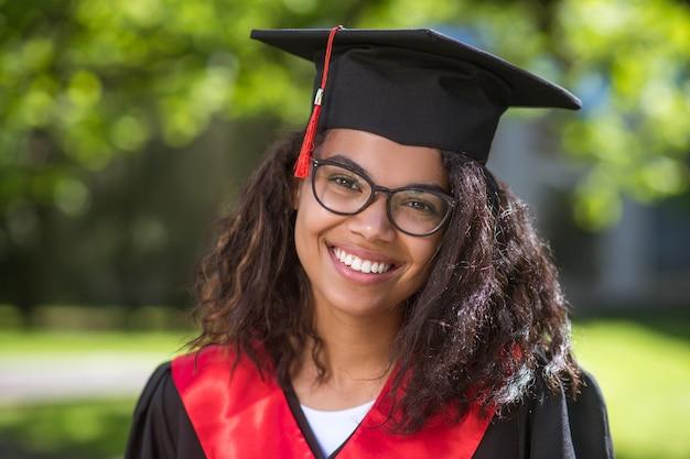Diploma uitreiking. vrij jong meisje met academische pet die blij is met afstuderen