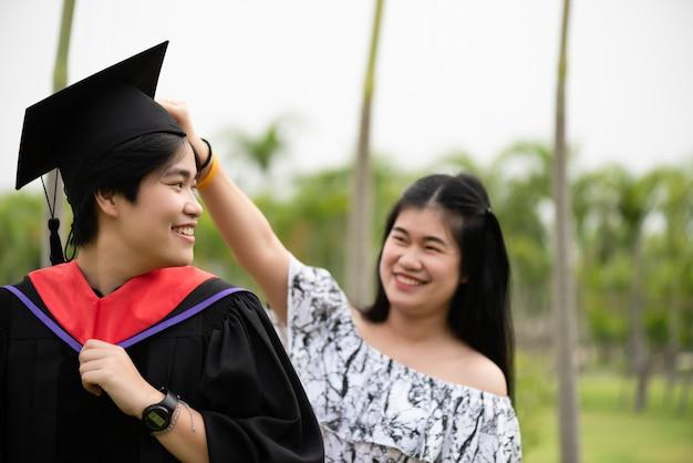 Diploma uitreiking. vrouwelijke afgestudeerde met haar vriend feliciteren