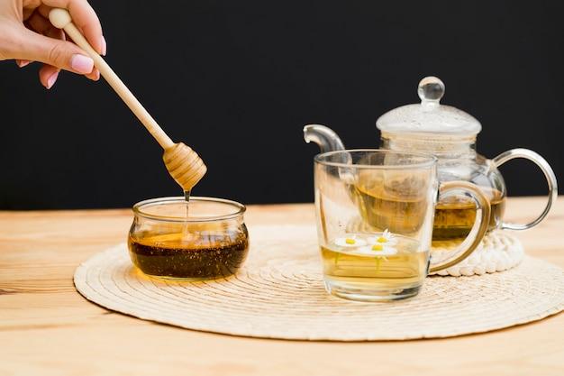 Dipper van de vrouwenholding over honingskruik dichtbij glas en theepot