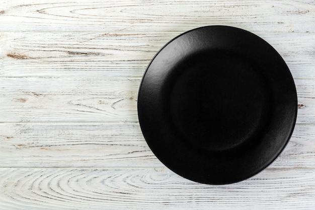 Direct boven lege zwarte matte plaat op wit hout