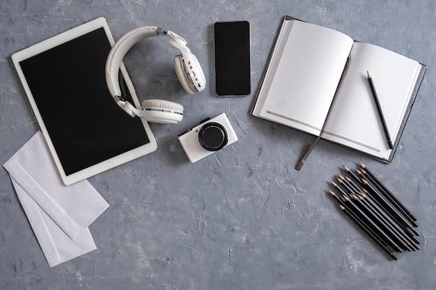 Direct boven schot van bureau en briefpapier op grijze achtergrond