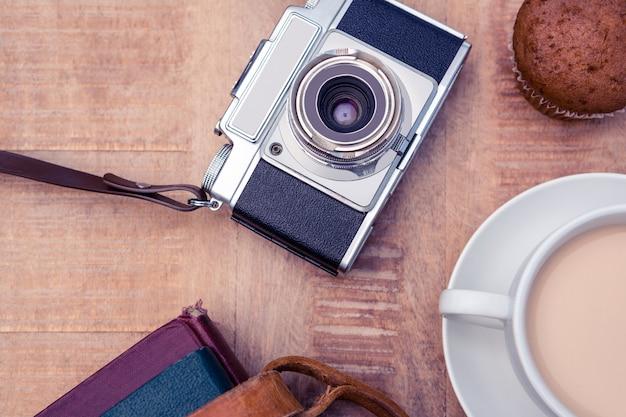 Direct boven shot van oude camera met dagboeken en koffie op tafel