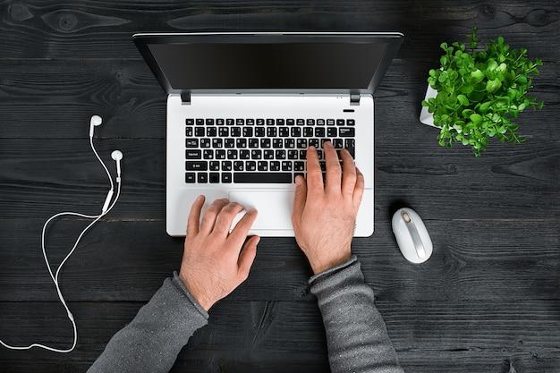Direct boven weergave van menselijke handen die op laptop typen
