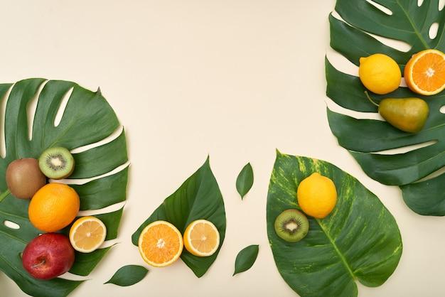 Direct boven weergave van vers rijp fruit op tropische bladeren op geïsoleerde achtergrond