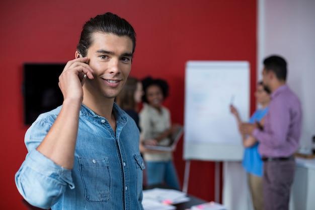 Directeur die op mobiele telefoon tijdens vergadering spreekt