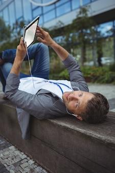 Directeur het luisteren muziek op digitale tablet