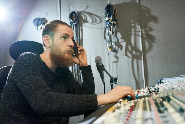 Directeur met koptelefoon in de opnamestudio