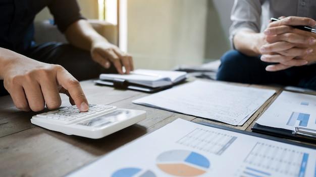 Directeuren die op taxatiedatadocument analyseren met calculator
