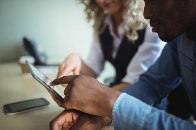 Directeuren die over digitale tablet bespreken