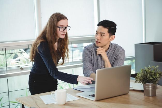 Directeuren die over laptop bespreken