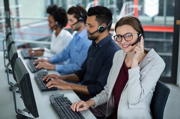 Directeuren met hoofdtelefoons die computers met behulp van bij bureau in bureau
