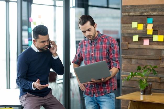 Directeuren met laptop bespreken op telefoon