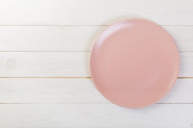 Directy boven lege roze matplaat op witte houten achtergrond met exemplaarruimte