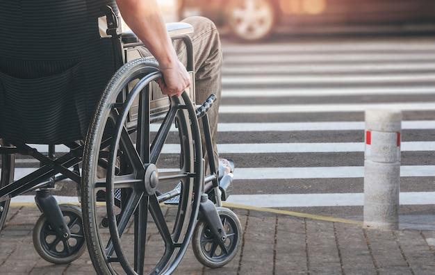 Disableemens op rolstoel die de weg kruisen.