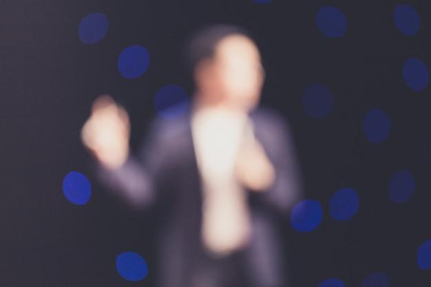 Disfocus van de spreker op het podium in een vergaderruimte