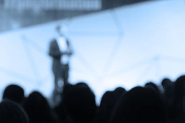 Disfocus van de spreker praten over zakelijke conferentie.