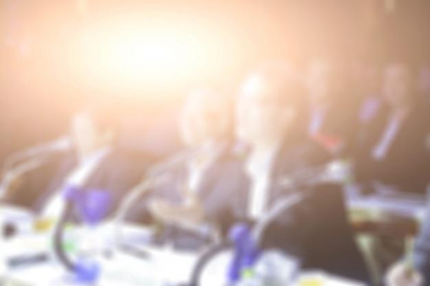 Disfocus van zakenman die een openbare toespraak in een conferentieruimte geeft