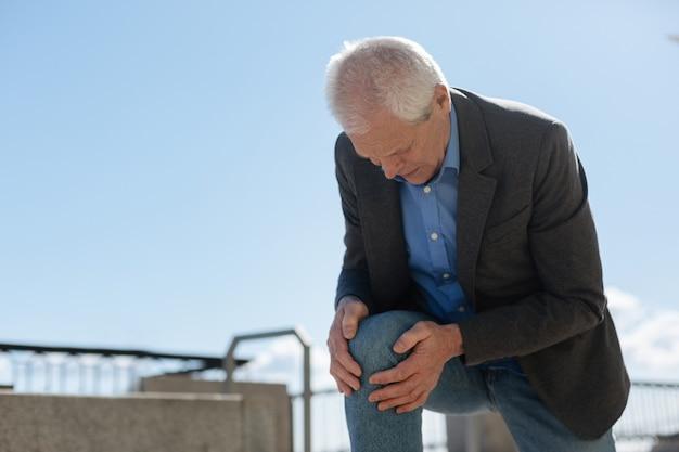 Dismal gefrustreerde oude man die zichzelf op zijn knie oprichtte terwijl hij zijn handen vasthield terwijl hij vreselijke pijn voelde