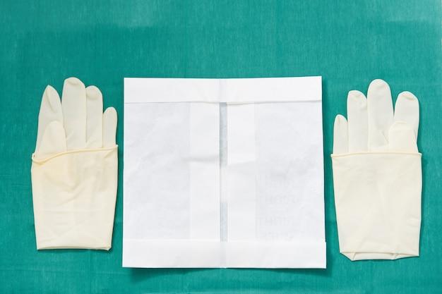 Disposible steriele rubber, eenmaal gebruikte handschoenen met papieren verpakking op groene handtekening van operatiekleding