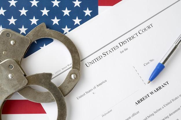 District court arrest warrant rechtbankpapieren met handboeien en blauwe pen op de vlag van verenigde staten. concept toestemming om verdachte te arresteren