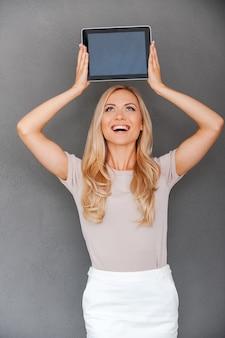Dit apparaat is geweldig. vrolijke jonge vrouw die digitale tablet boven haar hoofd houdt en omhoog kijkt