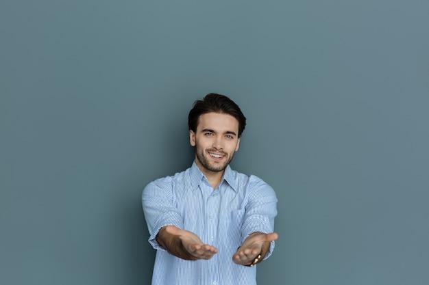 Dit ben ik. positief aardig knap en staand tegen een grijze achtergrond en je zijn handen laten zien terwijl je glimlacht